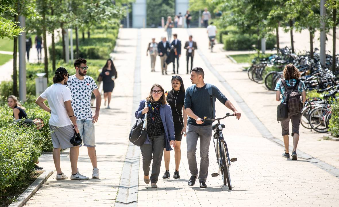 Students walking on campus with a bike