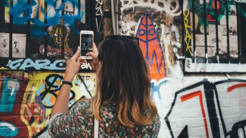 woman taking picture of street art with smartphone